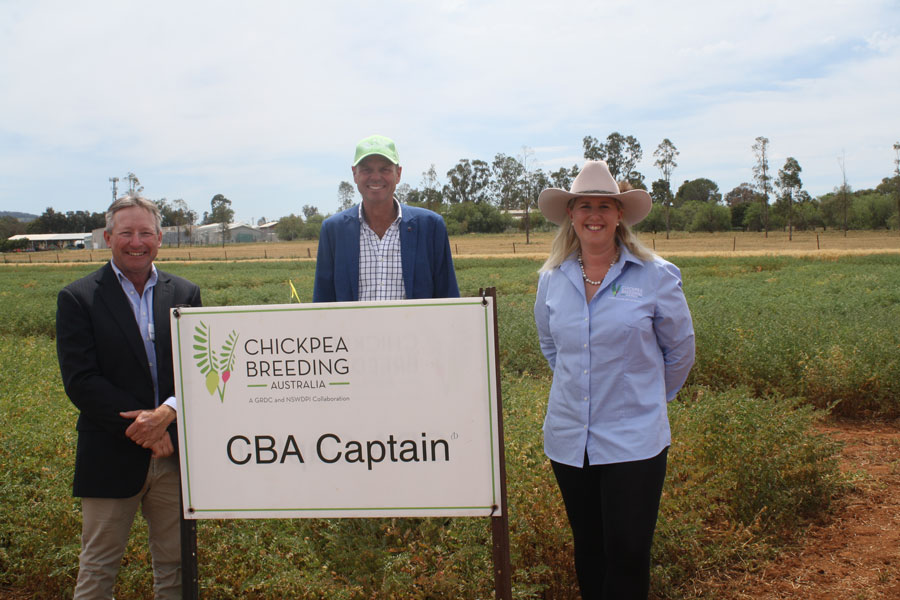 People standing in a field behind a billboard with CBA Captain written on it