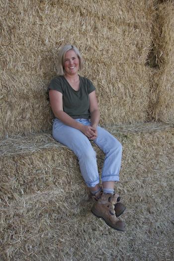 Lou Flohr sitting on hay bales.