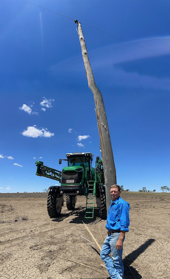Phil Crocker standing beside a power pole with his self-propelled sprayer